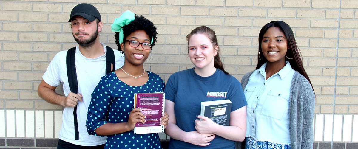 Four NCTC Students with textbooks on campus