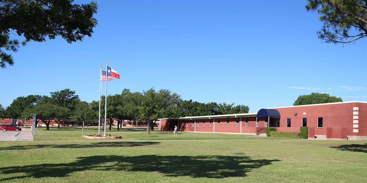 Gainesville Campus facade with flags and student.