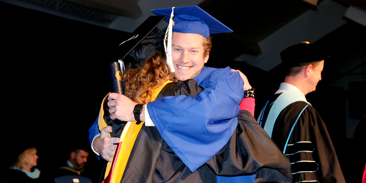 Proud graduate gives a hug to faculty member