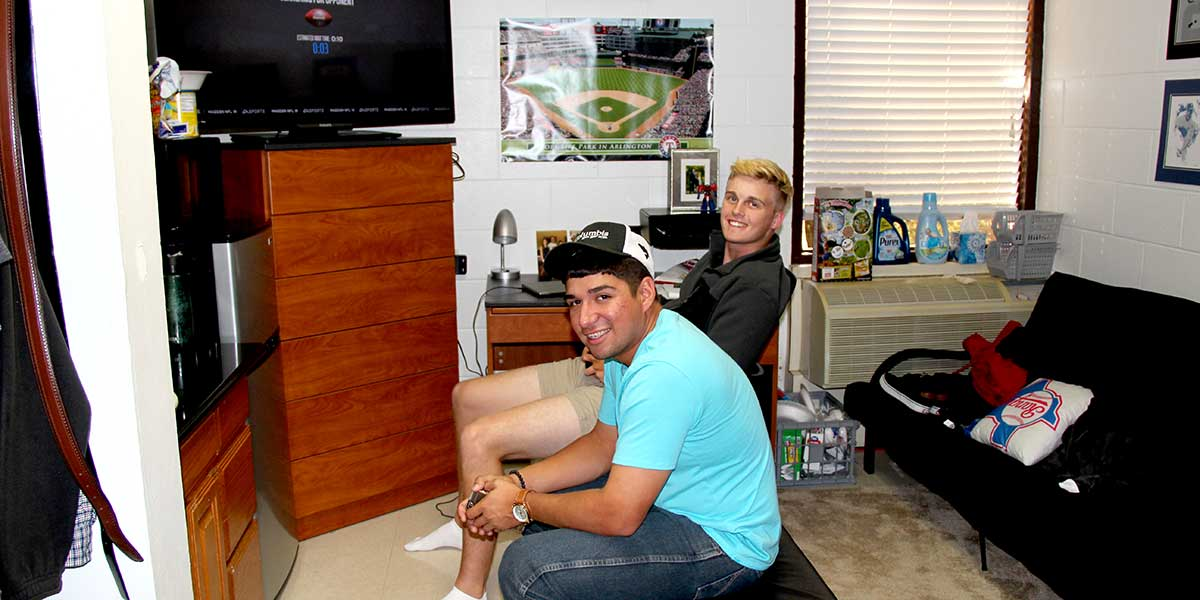 Two students playing video games in a dorm room